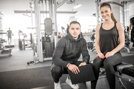 fitness trainer: Young male personal fitness trainer talks to his female client and giving her advices for motivation.