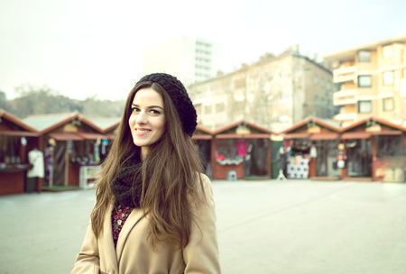 Young pretty adult woman standing on holiday market during Christmas time in Sarajevo, Bosnia and Herzegovina. Toned image.