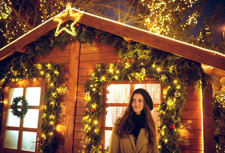 Pretty young brunette woman standing in front of Santa Claus house at Christmas Holiday Market in Sarajevo, Bosnia during december evening. Toned image. High ISO.