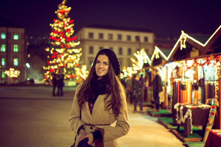 Pretty young adult woman standing in Christmas Holiday Market during cold evening in Sarajevo, Bosnia and Herzegovina and visiting street shop stalls. Christmas lights in backgroud. Toned image. High ISO. Stock Photo