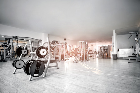 Equipment And Machines At The Empty Modern Gym Room. Fitness Center. Toned image. Archivio Fotografico