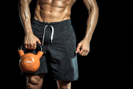 Handsome bodybuilder standing with kettlebell in hands. Isolated.