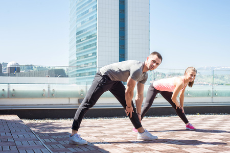 Young fitness couple stretching on rooftop of building while preparing for serious exercise.