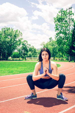 Young adult slim fit girl doing some stretching relaxing exercises on athletic track during hot summer day.