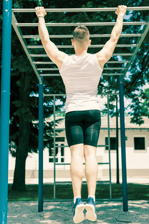 Muscular man doing pull-ups in outdoor gym park during bright hot summer day. Toned image.
