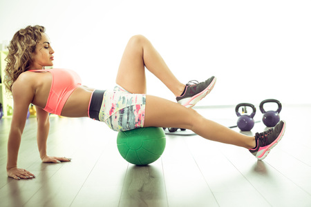 laying abs exercise: Slim woman in 30 doing stretching exercises with medicine ball in bright fitness center