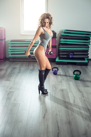 Sexy attractive woman doing biceps curls with dumbbell in modern gym wearing grey bodysuit and high heel boots. Toned image. 版權商用圖片