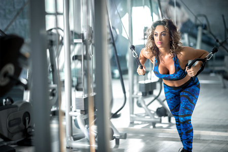Young attractive woman with curly hair doing cable fly exercise in lunge position in modern bright fitness center. Toned image.