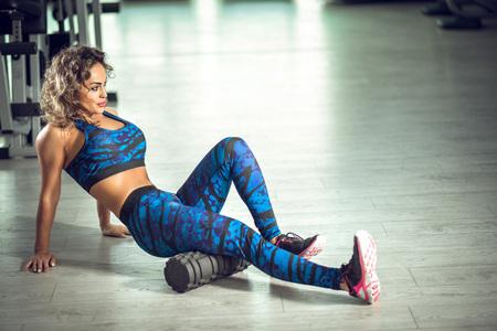 busty: Atractiva mujer haciendo ejercicios de rodillo de espuma y posando en el moderno gimnasio brillante. Imagen tonificada.