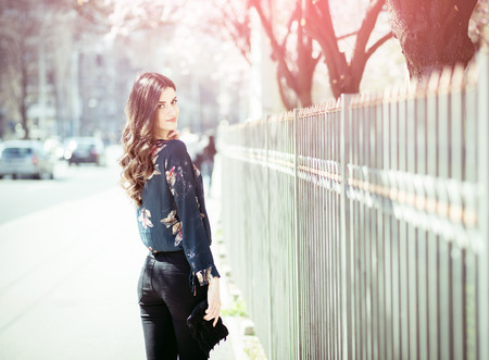 Young beautiful brunette in 20s wearing fashionable modern clothes on the streets of Sarajevo, Bosnia during spring blossom day. Toned image. Stock Photo