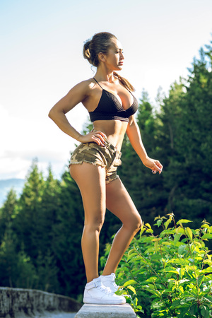 Attractive woman in 30s standing posing in forest wearing sport military pattern clothes. Toned image. Stock Photo