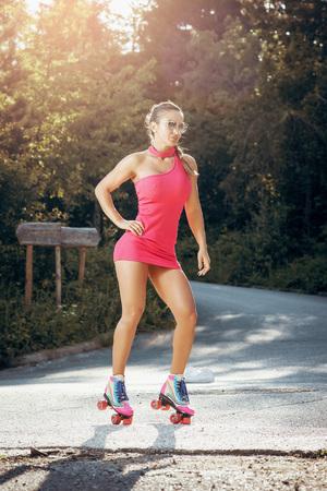 Atractiva mujer sexy en 30s de pie sobre el asfalto con vestido de neón brillante de color rosa y patines. Imagen tonificada. Foto de archivo