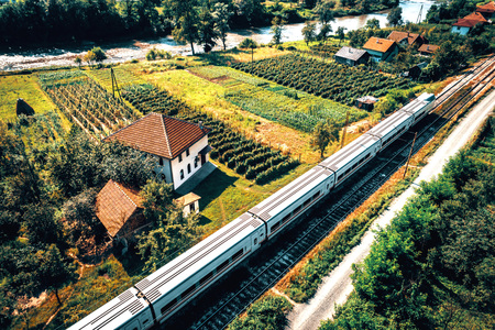 balkans: Aerial view of modern Talgo train passing by masjid and raspberry plants in Begov Han, Zepce, Bosnia and Herzegovina. Toned image.