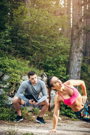 Persoonlijke trainer die zijn plankoefening toont aan zijn vrouwelijke klant. Getoonde afbeelding. Stockfoto