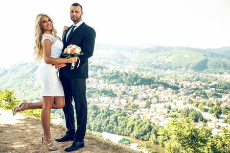 Attractive wedding couple posing on hill above Sarajevo. Toned image. Stock Photo