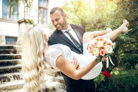 Attractive handsome groom carrying his blonde beautiful bride in botanic garden of National Museum in Sarajevo. Toned image.