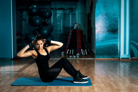 laying abs exercise: Young attractive brunette doing crunches exercise in modern gym. Toned image. Stock Photo