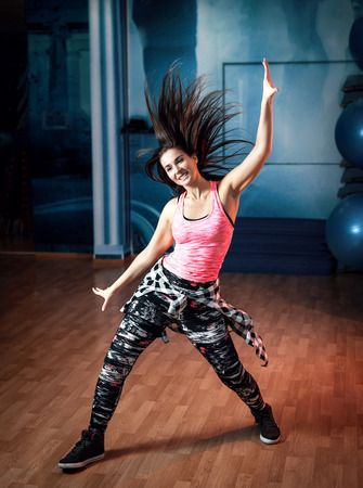 Young attractive brunette woman doing zumba dance workout alone in gym. Toned image. Standard-Bild