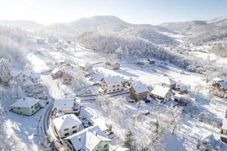Village Ozimica in Zepce area, Bosnia and Herzegovina during snowy winter holiday season. Toned image.