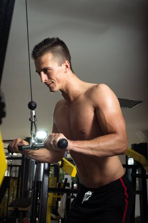 Young adult man doing cable pull down triceps exercise in gym Standard-Bild
