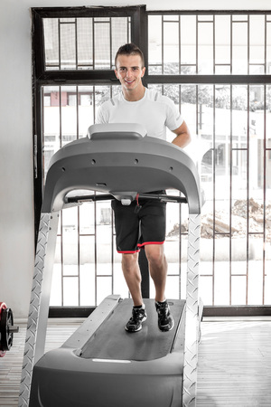 Young fit adult man running on treadmill in gym