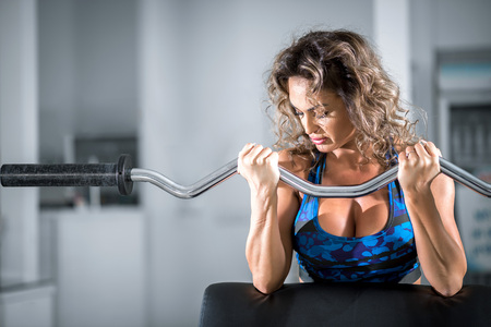 Attractive woman with curly hair doing preacher curl biceps exercise on bench with EZ curl bar in modern fitness center. Toned image.