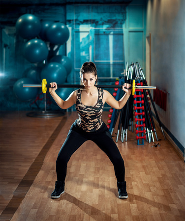 Young adult attractive brunette doing squat exercise in modern gym. Toned image. Stock Photo