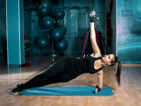 Attractive brunette doing side plank exercise in blue gym. Toned image.