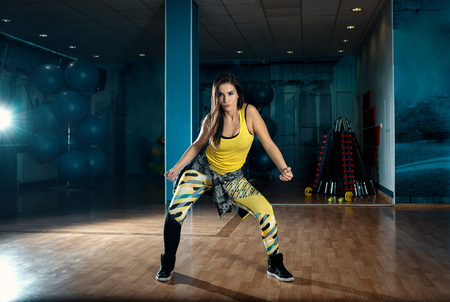 Young attractive brunette woman doing zumba dance workout alone in gym. Toned image. Stock Photo