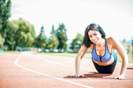 Young woman doing push ups exercise outdoor on running track in park. Toned image. Stock Photo