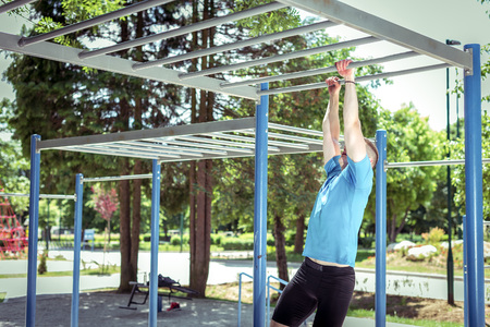 Young adult man doing outdoor gym fitness exercises hanging on monkey bars in park. Toned image.