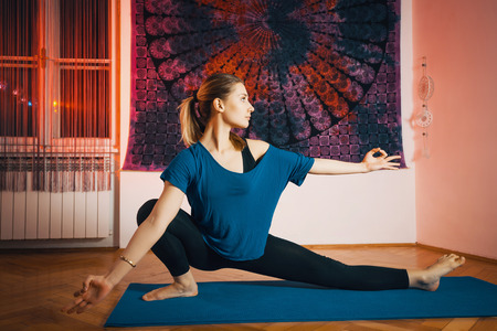 Portrait of gorgeous young woman practicing yoga indoor. Beautiful girl practice yoga in peaceful ambient. Calmness and relax, female happiness.