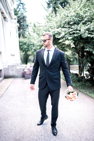Young attractive handsome elegant man holding flower bouquet in his had. Toned image.