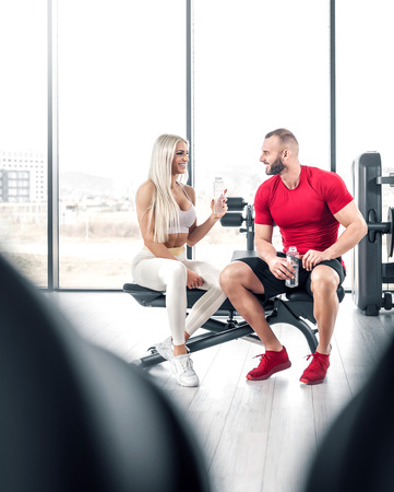 Young attractive fitness couple drinking water from plastic bottle while sitting on bench in modern bright gym. Toned image.