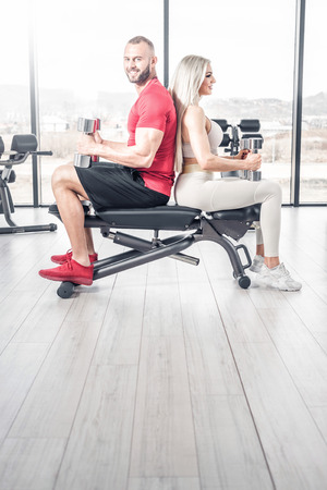 Attractive fitness couple doing some light exercises with dumbbells in modern bright gym. Toned image.