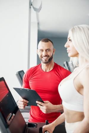 Young male fitness instructor teaching his blonde female client to walk on treadmill and watching her progress. Toned image. Standard-Bild