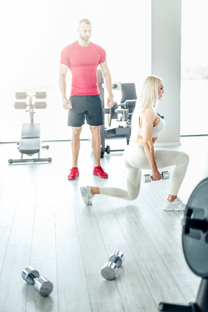 Young attractive blonde female doing lunge exercise in modern bright fitness center with assistance of her personal trainer.  Toned image.