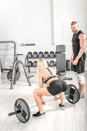 Attractive blonde woman doing barbell deadlift exercise with help of her personal trainer in bright modern gym. Toned image.