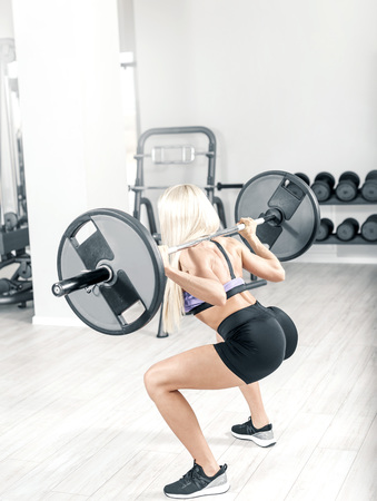 Young attractive blonde woman doing squats in modern bright gym. Toned image.