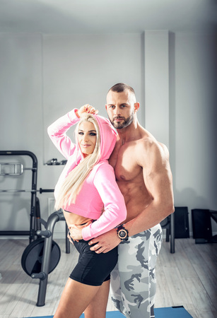 Attractive fit couple posing together in modern bright fitness center. Toned image.