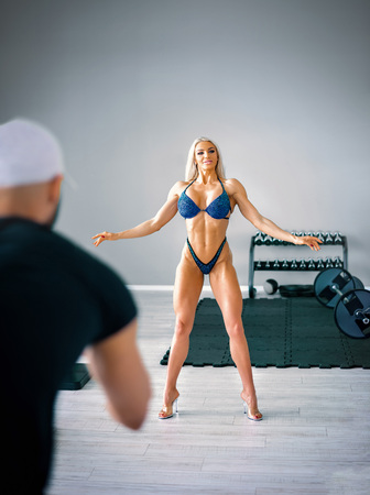 Attractive woman bikini bodybuilding professional practicing stage performance in gym with her coach. Toned image.