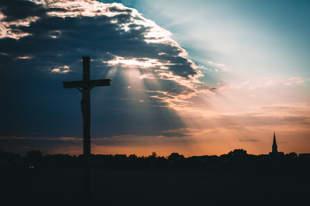 Jesus Christ on the cross, sunset in the background with clouds, rays of light and church