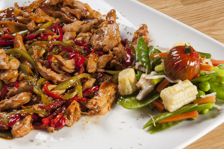 closeup view of chicken fajitas on white serving plate with garniture. Colorful vegetebles on plate, closeup view Stok Fotoğraf