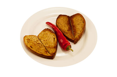 hot red pepper on a white plate with two heart-shaped toast photo