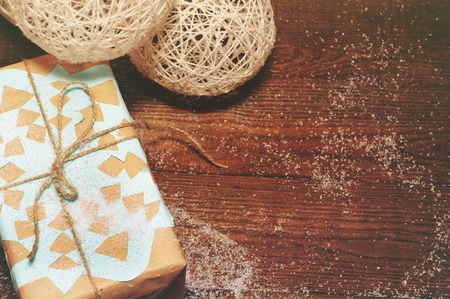 kinfolk: Christmas gift lies on a wooden table packed in kraft paper with a blue snowflake