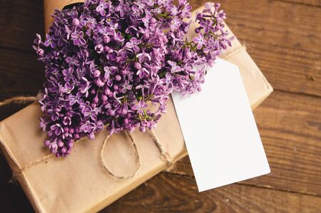 Bouquet of lilacs on a wooden table with a gift box of kraft paper Stock Photo