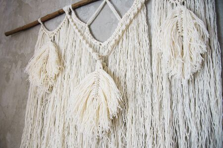 Wall panel in the style of Boho made of cotton threads in natural color using the macrame technique for home decor and wedding decoration. Beautiful boho macrame wall panel will add a cozy atmosphere and charm to any space in your home Stock Photo