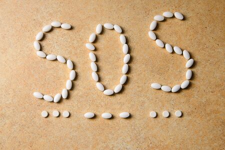 white vitamin D pills lie on the background of a concrete countertop lined with the word sos morse Stock Photo