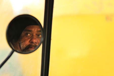 New Delhi, India � February 25, 2012: Reflection of drivers face in the rickshaw rear vision mirror driving in New Delhi, National Capital Region, North India