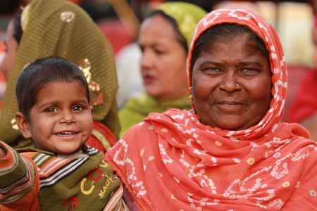 JAIPUR, INDIA Ð MARCH 4: An unidentified woman and child outside the City Palace on March 4, 2012 ahead of the annual Holi Festival in Jaipur, Rajasthan, Northern India. The City Palace includes the Chandra Mahal and Mubarak Mahal palaces.